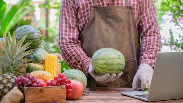 Granjero vende fruta fresca en línea. concepto de compras en línea y entrega a domicilio. nueva vida normal y negocios después de covid-19. bloqueo y autocuarentena.