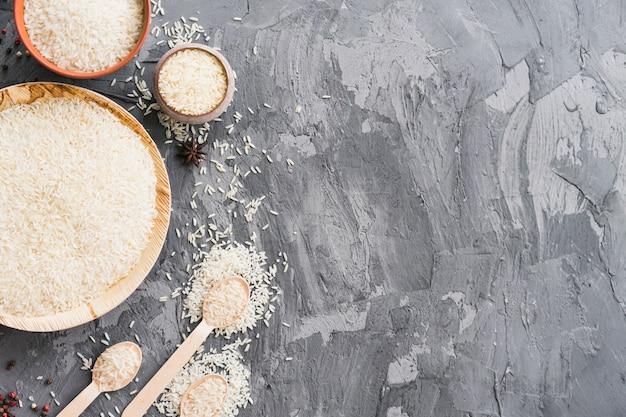 Grano de arroz crudo orgánico en placa de madera; tazón y cuchara sobre papel tapiz de hormigón texturado