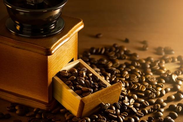 Grano de café en la bandeja del molinillo en la mesa y la luz de la mañana.