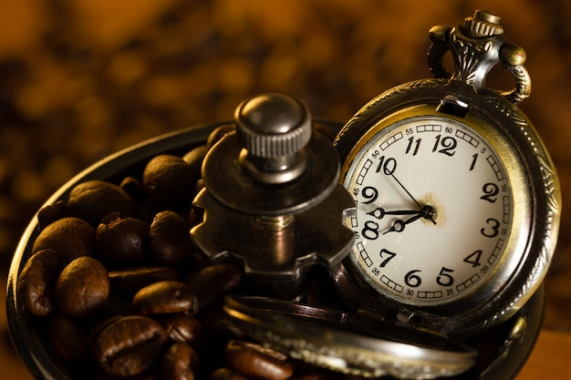El grano de café y el bolsillo miran la bandeja del molinillo manual en la mesa. primer plano y copia espacio. concepto de tiempo de café en la mañana.