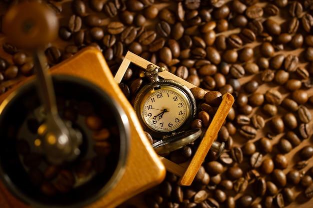 El grano de café y el bolsillo miran la bandeja del molinillo manual en la mesa.