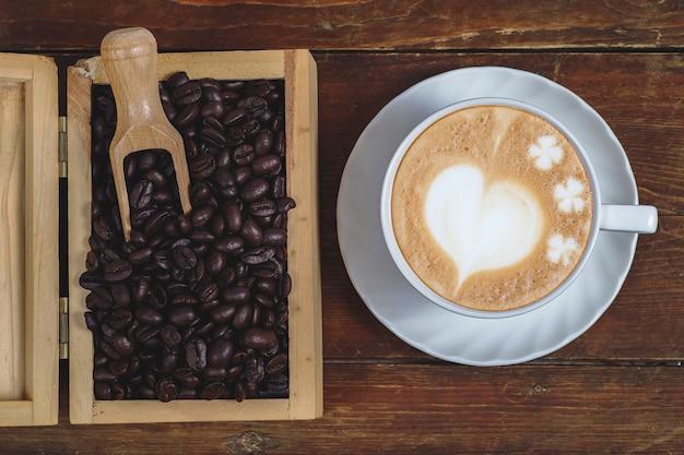 Grano de café en caja de madera con café de arte tardío sobre fondo de madera vieja.