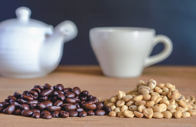 Grano de café crudo y tostadores de grano de café sobre la mesa.