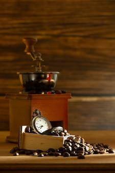 Grano de café y reloj de bolsillo. amoladora manual en la mesa en la mañana.
