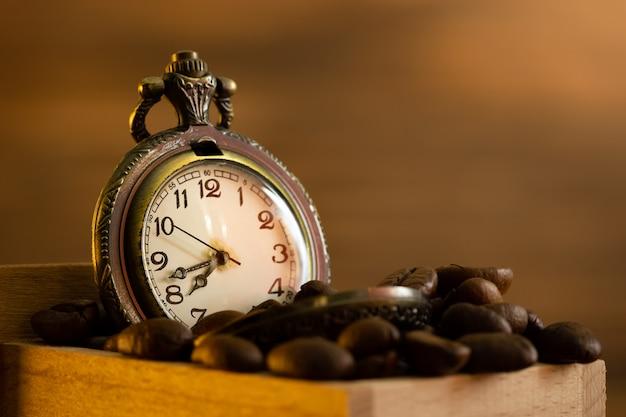 Grano de café y reloj de bolsillo en molinillo manual sobre mesa. primer plano y copyspace. hora del café en la mañana.