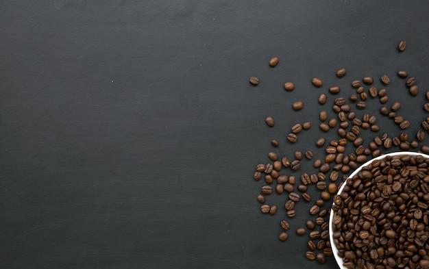 Grano de café en taza blanca sobre piso de madera negra