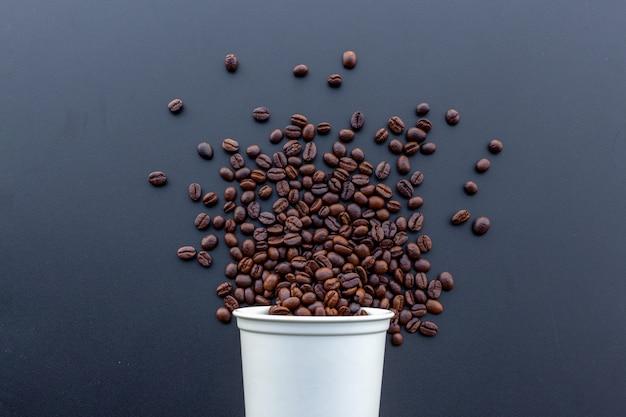 Grano de café en la taza caliente blanca en fondo del escritorio
