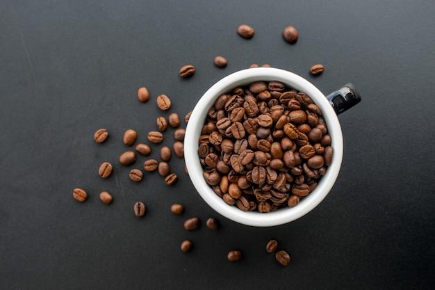 Grano de café en taza en fondo negro