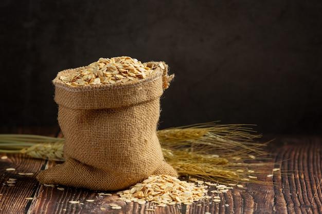 Grano de cebada cruda en fondo de madera