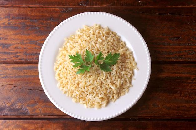 Grano orgánico del arroz moreno cocinado en el plato blanco. arroz integral