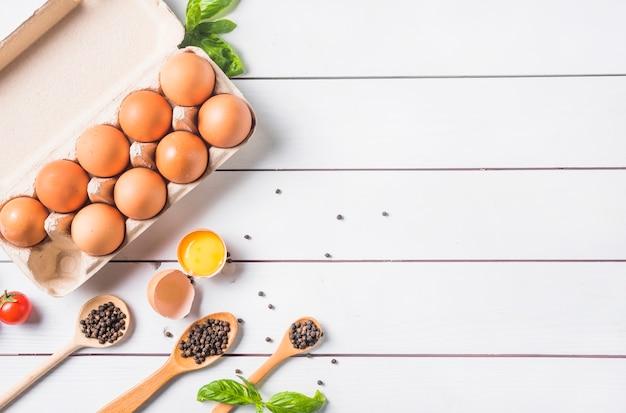 Grano de pimienta en cuchara de madera con hojas de albahaca y huevos en cartón