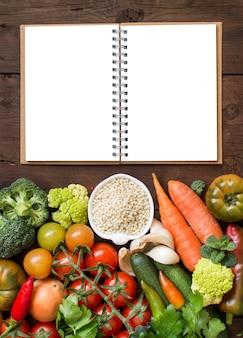 Grano de sorgo blanco en un recipiente con verduras y cuaderno en la vista superior de madera