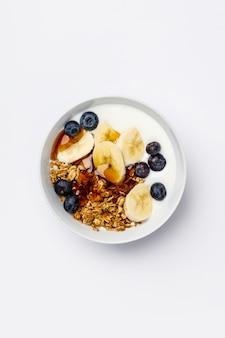 Granola de avena con arándanos frescos, plátano, yogur y jarabe de arce