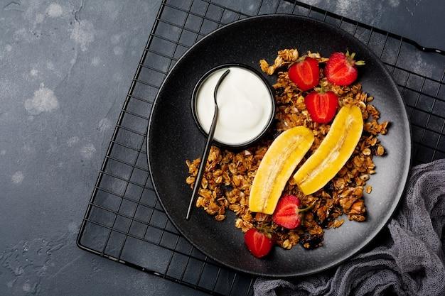 Granola de avena con yogur, fresas frescas y plátano, semillas de chía, girasol y miel en plato de cerámica negra. vista superior.