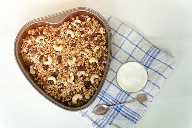 Granola en una bandeja para hornear y yogur sobre un fondo blanco claro.
