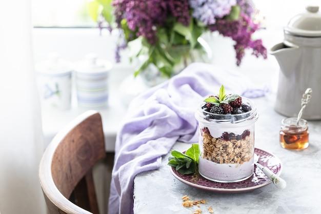 Granola casera en un frasco con yogur griego y moras y frambuesas sobre la mesa con lila.