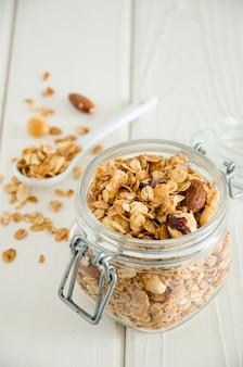 Granola casera multigrano con una mezcla de nueces en un frasco sobre una superficie de madera blanca