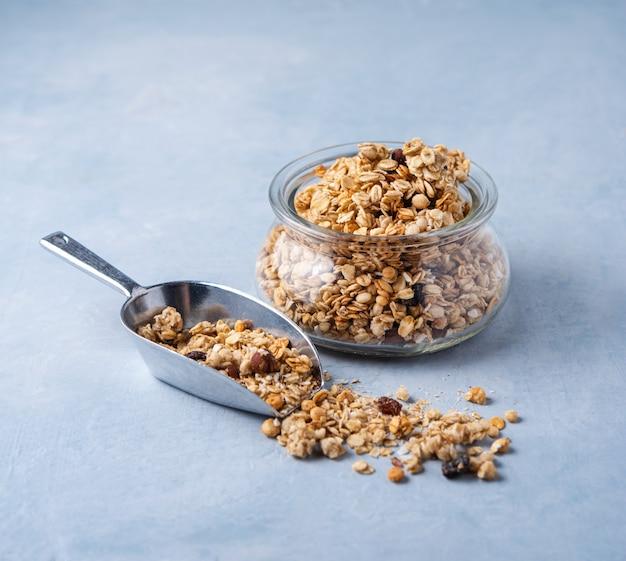 Granola casera con nueces en un frasco de vidrio sobre fondo azul comida vegana saludable