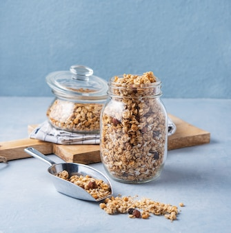 Granola casera con nueces en un frasco de vidrio sobre fondo azul merienda vegana saludable
