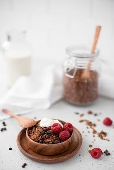 Granola de chocolate con yogur griego y frambuesas en un cuenco de madera, close-up