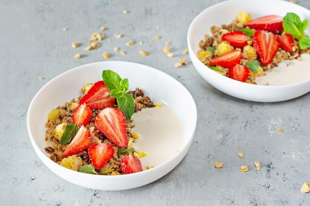 Granola crujiente casera con nueces, frutos secos, fresas frescas, menta y yogur