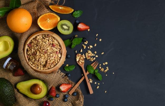 Granola en cuenco de madera y frutas en piedra negra.
