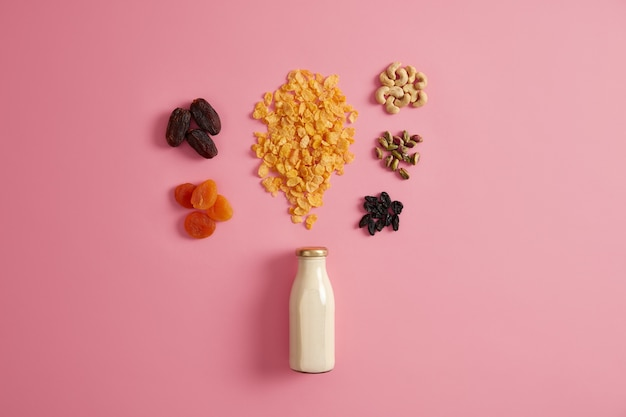 Granola de desayuno saludable. cereales con botella de leche fresca, frutos secos y nueces nutritivas para preparar un delicioso refrigerio nutritivo para tener energía durante todo el día. concepto de dieta y alimentación limpia.