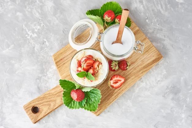 Granola o yogurt con fresa en vidrio, bayas frescas y frasco con azúcar en una tabla de cortar, vista superior