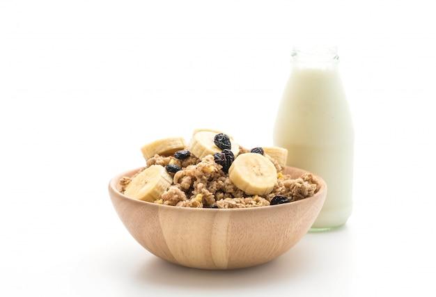 Granola con plátano, pasas y leche para el desayuno.