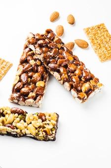 Granola; semillas de sésamo y barras de almendras sobre fondo blanco