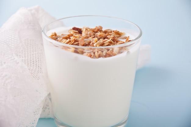 Granola con el yogur en vidrio con la cuchara de madera en una tabla.