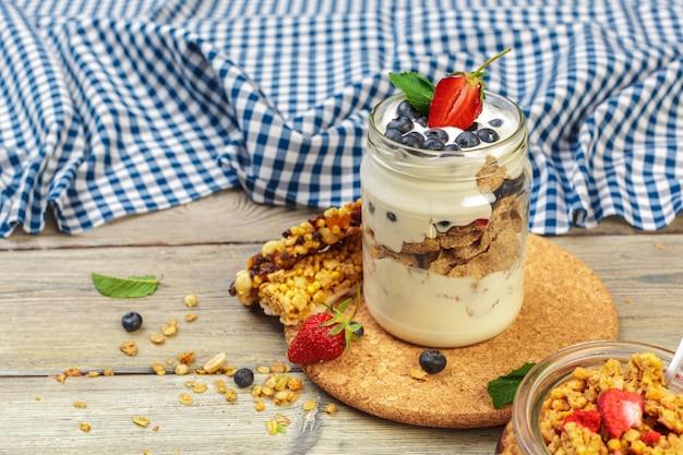 Granola, yogurt y fresas en frascos