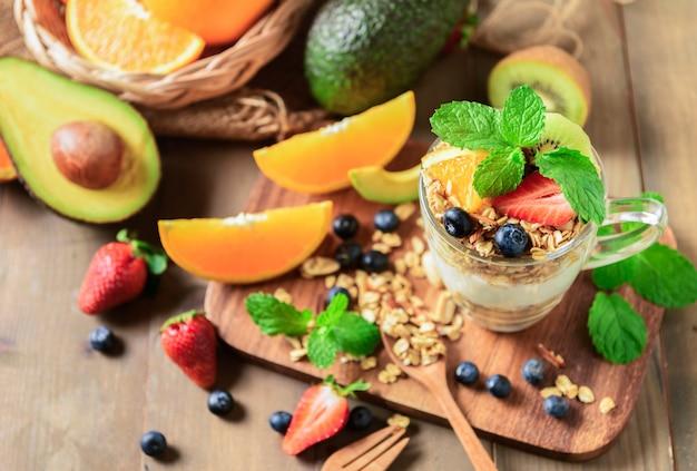 Granola y yogurt y frutas sobre cobertura en vaso.