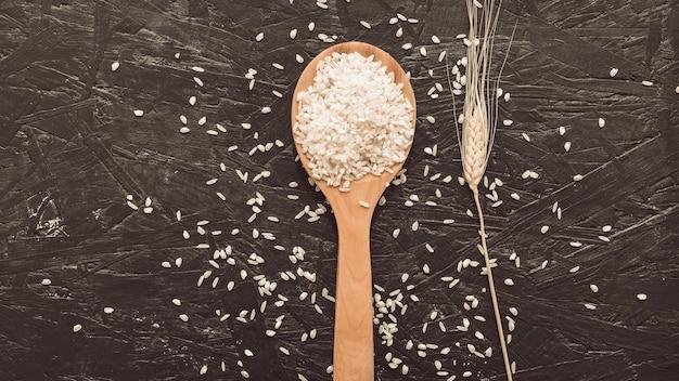 Granos de arroz blanco en cuchara de madera sobre fondo gris áspero