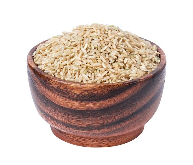 Granos de arroz integral en un tazón de madera aislado en blanco