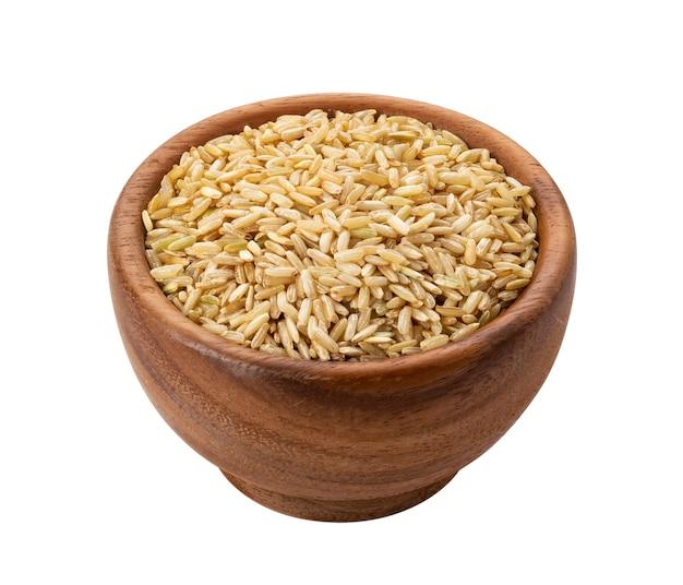 Granos de arroz integral en un tazón de madera aislado