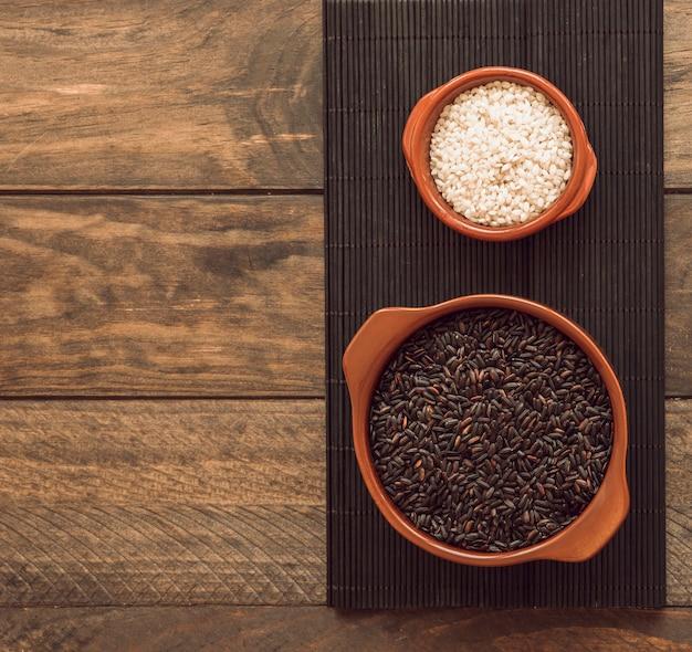 Granos de arroz marrón y blanco en el recipiente en la bandeja sobre la mesa de madera