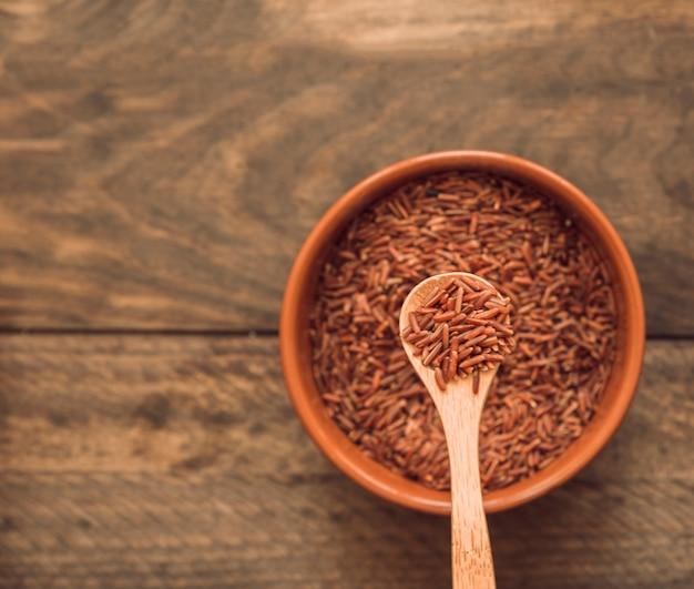 Granos de arroz rojo jazmín en una cuchara sobre el recipiente contra el fondo de madera