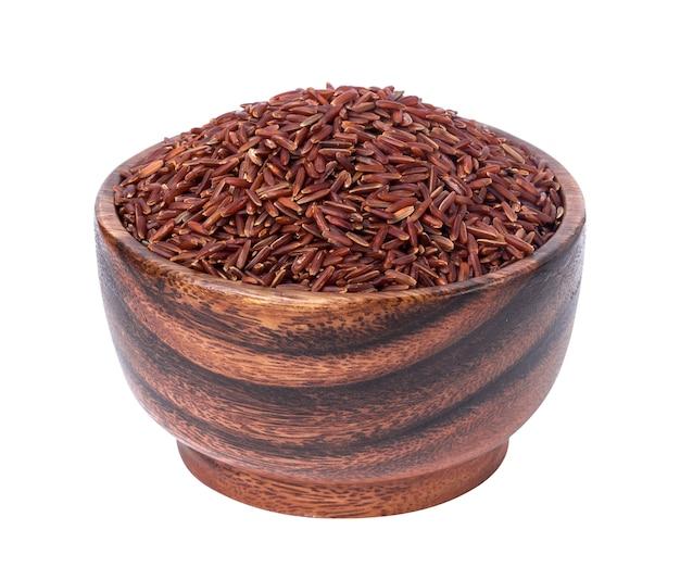 Granos de arroz rojo en un tazón de madera aislado en blanco