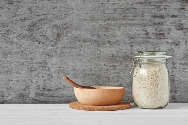 Granos de arroz en tarro de cristal y cuenco de madera