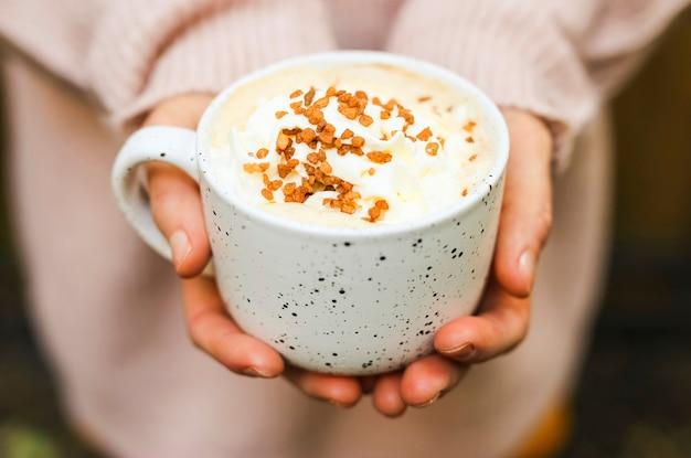 Granos de azúcar moreno en espuma de café en una taza de cerámica blanca