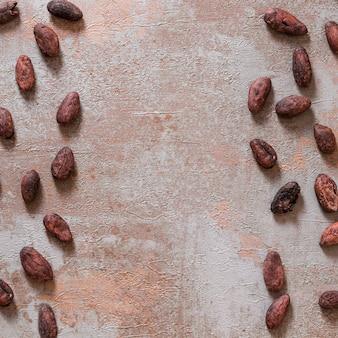 Granos de cacao entero en el fondo rústico