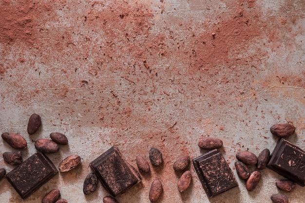 Granos de cacao y polvo con trozos de barra de chocolate sobre un fondo antiguo