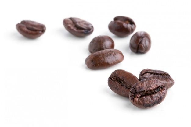 Granos de café aislados en el fondo blanco.