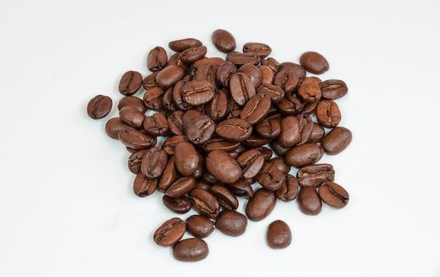 Granos de café aislados en una superficie blanca.
