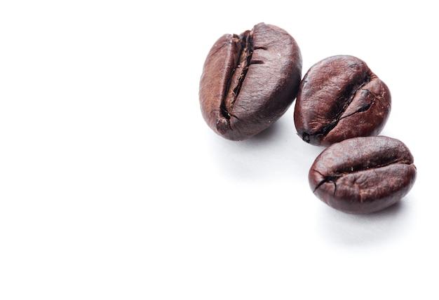 Granos de café aislados en superficie blanca y