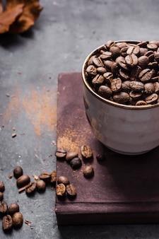 Granos de café de ángulo alto en taza sobre tabla de cortar