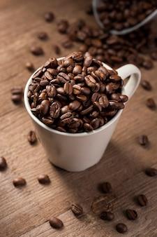 Granos de café de ángulo alto en taza