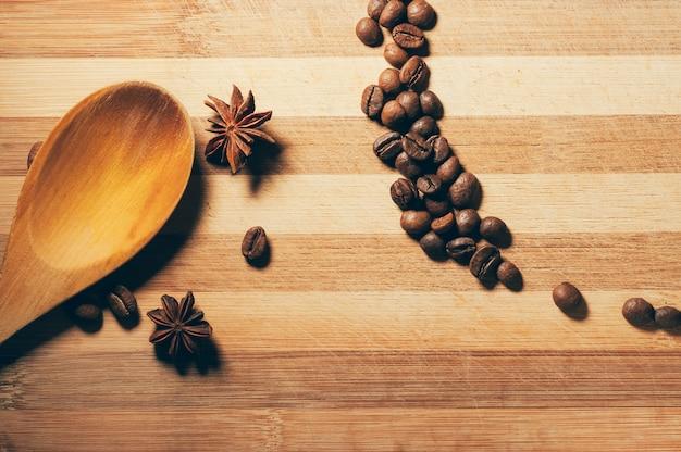 Granos de café con anís y cuchara de madera.