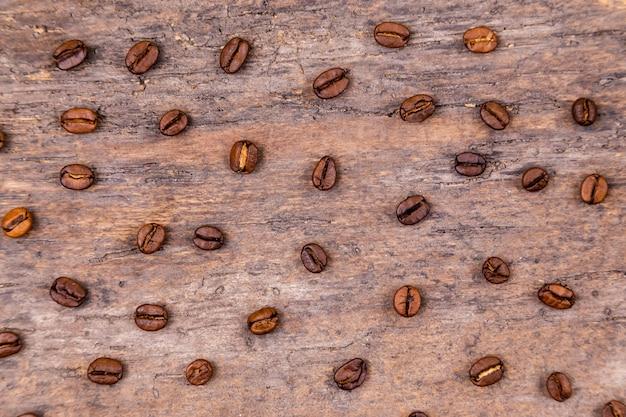 Granos de café aromáticos en la mesa de madera blanca. vista superior. bandera